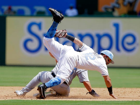 Texas Rangers second baseman Rougned Odor (12) is upended after tagging out Seattle Mariners' Danny Valencia on a steal attempt in the third inning of a baseball game, Sunday, June 18, 2017, in Arlington, Texas. (AP Photo/Tony Gutierrez)