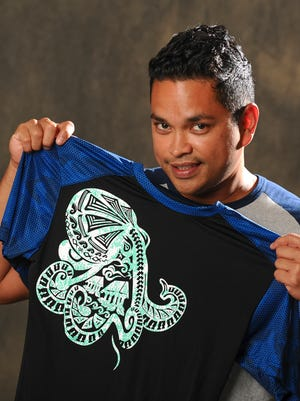 Clothing designer Raymond Anderson displays a quick dry shirt with a gamson, or octopus, graphic that incorporates imagery of latte stones, huts and other iconic Chamorro designs, during a photo shoot in Hagatna on Friday, May 20.