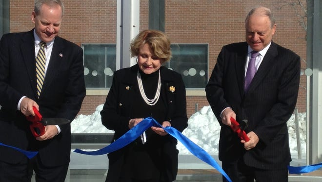 Bill Carpenter of RGRTA, left, Rep. Louise Slaughter and Peter Robinson of URMC, right, cut a ribbon at a new bus shelter on the medical campus Thursday, Feb. 18, 2016.