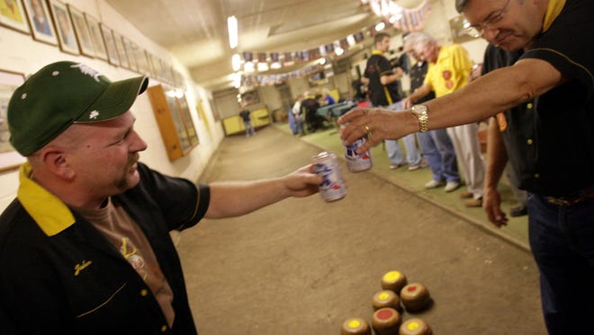 October 2007: John Marlin, 42, of Harper Woods, shares a  beer toast with Lou Danckaert, 64, of Eastpointe, during a game of feather bowling at Cadieux Cafe in Detroit. Danckaert had just scored two points for the team. In 2017, Cadieux Cafe is still a fixture for mussels, beers and the Belgian sport.