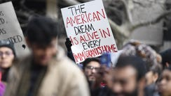 "A protester holds a sign that reads, ""The American"