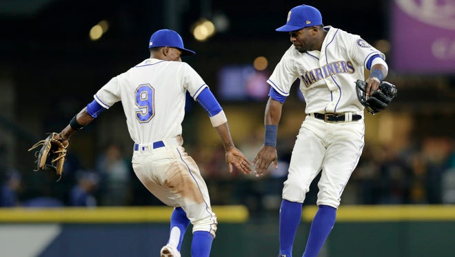 Dee Gordon, left, and Guillermo Heredia celebrate a win over the Tampa Bay Rays on Sunday. (AP Photo/John Froschauer)
