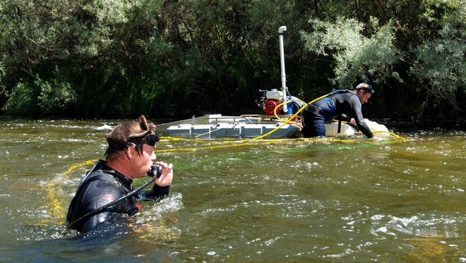 In this 2009 photo, Aaron Webb of Rapids, Wis., (left) and Matt Lauer of Portage, Wis., team up to hunt for gold with a suction dredge on the Klamath River near Happy Camp, Calif.