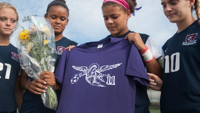 Captains of the Eastern varsity girls soccer team, from left, Katie Beluch, Sydney Davis, Jaylyn Thompson, and Rachel Wood stand with flowers and a shirt given to them before Mondays game by the captains of the Camden Catholic girls soccer team in honor of Eastern freshman soccer player Kara Lemanowicz, who died suddenly in early September.  09.28.15