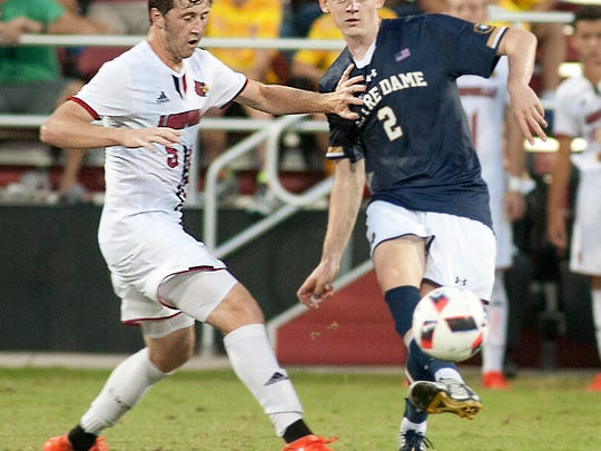 Louisville Cardinals midfielder Jack Gayton pushes aside Notre Dame midfielder Tommy McCabe as they fight for the ball.