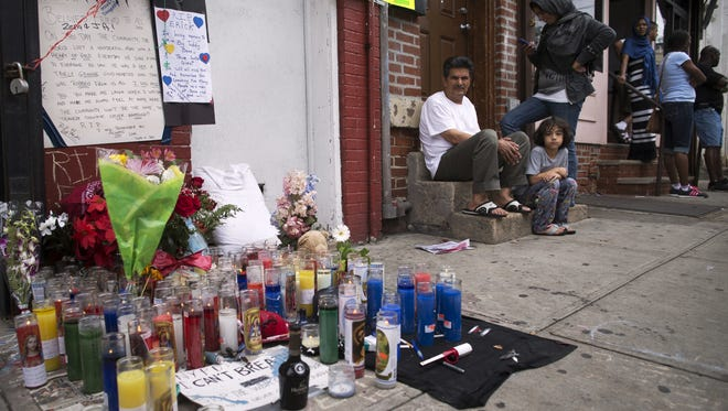 Pedestrians sit near a memorial for Eric Garner erected near the site of his death, Saturday, July 19, 2014.