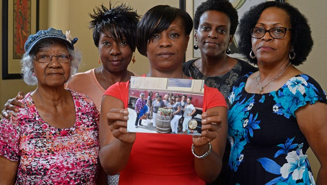 Five members of the Sistahs on the Reading Edge book club, all of Antioch, from left, Katherine Neal, Georgia Lewis, Lisa Renee Johnson, Allisa Carr and Sandra Jamerson stand together at Johnson's home in Antioch, Calif., on Monday, Aug. 24. The five women were among 11 African-American women who were were booted off the Napa Valley Wine Train on Saturday afternoon. Johnson holds a photograph of the group that was taken before boarding the train.