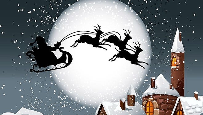 Santa Claus flies through the air with the reindeer pulling his sled.