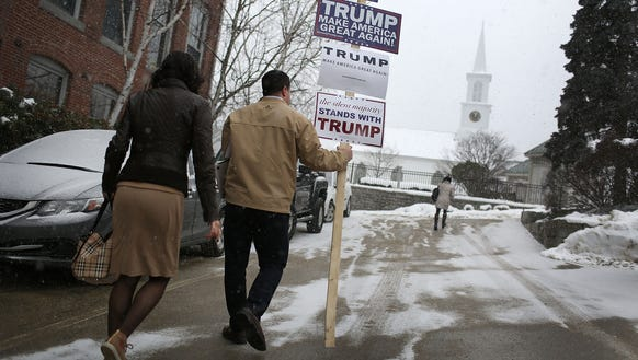 Gilead Towne carries a campaign sign supporting Donald