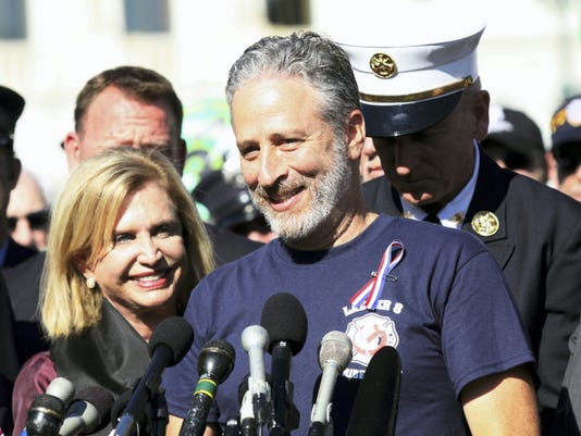 Comedian Jon Stewart, accompanied by Rep. Carolyn Maloney, D-N,Y., and New York City first responders, speaks during a rally Wednesday in Washington, D.C., calling for the extension of the act that provides health care and compensation to 9/11 first responders and victims.