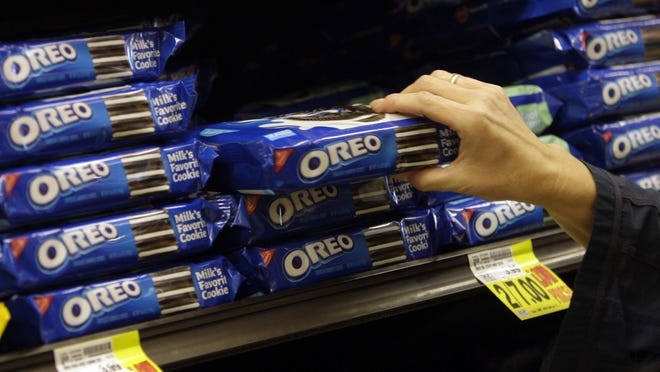 FILE - In this Feb. 9, 2011, file photo, a shopper selects Oreo cookies at a Ralphs Fresh Fare supermarket in Los Angeles. Activist investor Bill Ackman is paying approximately $5.5 billion for a 7.5 percent stake in Mondelez International Inc., the maker of products, including Oreo cookies and Cadbury chocolate, according to reports, Thursday, Aug. 6, 2015. (AP Photo/File)