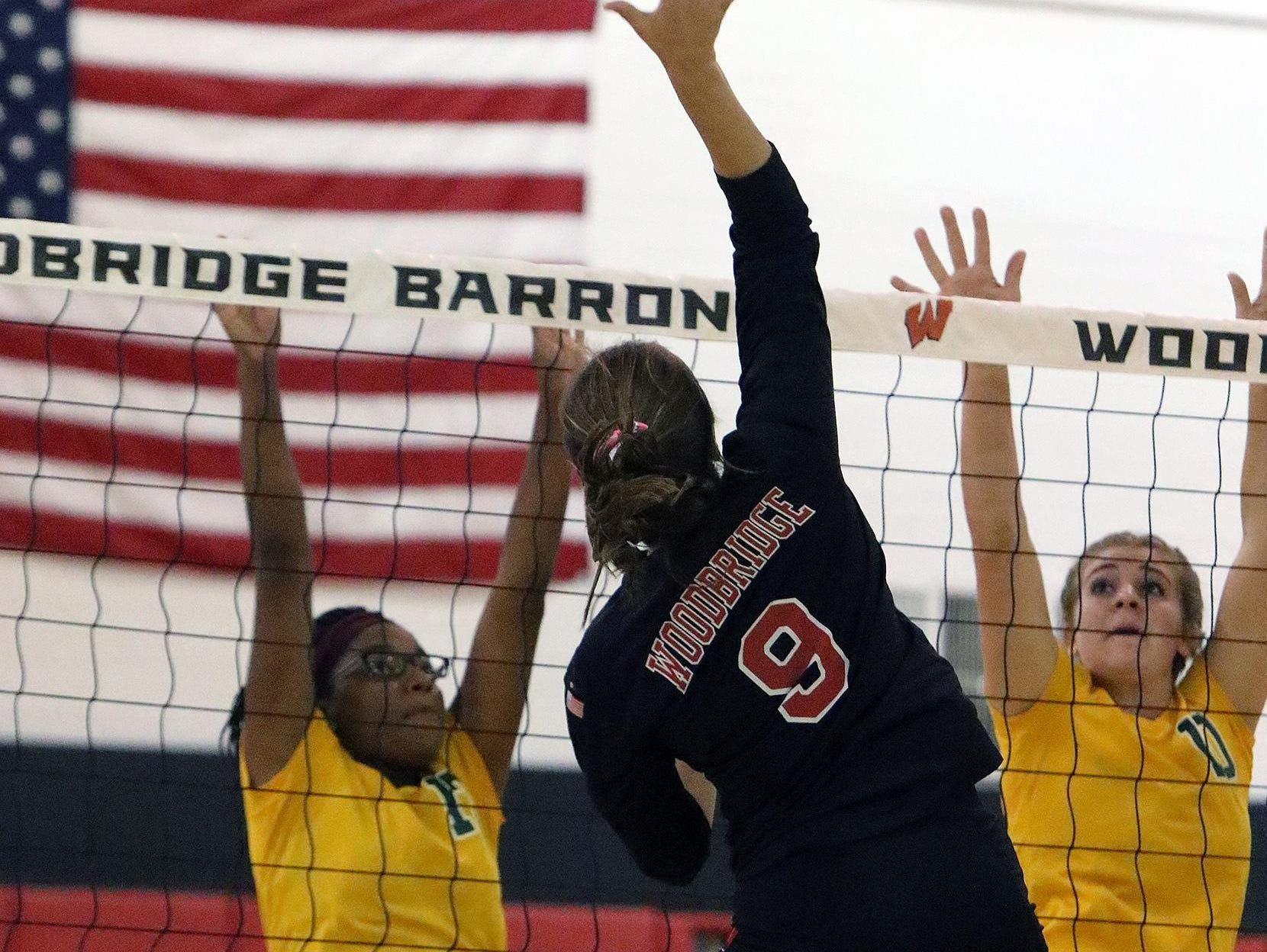 J.P. Stevens' Kassy Valbrun (13) and Rebecca Diserio (10) get up against Woodbridge's Azra Kukuljac (9) on Wednesday at Woodbridge High School.