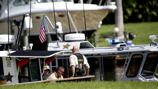 Members of the Lee County Sheriff's Office investigate a body found floating in the Caloosahatchee River on Monday.