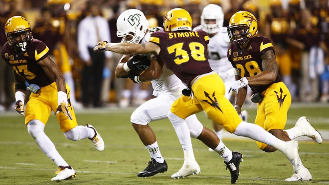 ASU's Jordan Simone tries to bring down Cal Poly Jared Mohamed after he run for a firstdown at Sun Devil Stadium on Sep. 12, 2015 in Tempe, AZ.