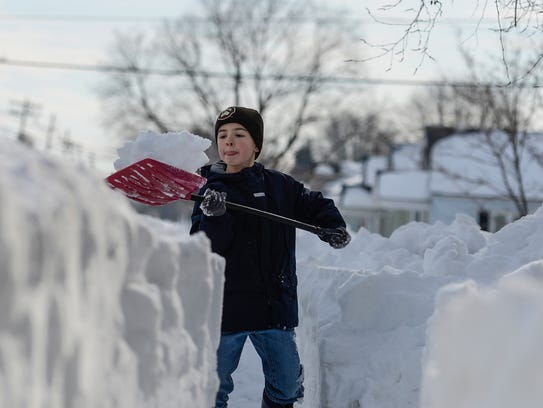 Cian Soliday, 8, shovels a path for the mailman at
