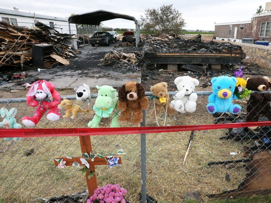 Stuffed animals line the chain link fence Monday where