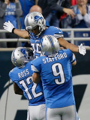 Detroit Lions Jeremy Ross lifts Golden Tate in the as quarterback Matthew Stafford runs up air after Tate scored his touch down to pull with in six points of the New Orleans Saints in Detroit on Sunday, October 19, 2014.