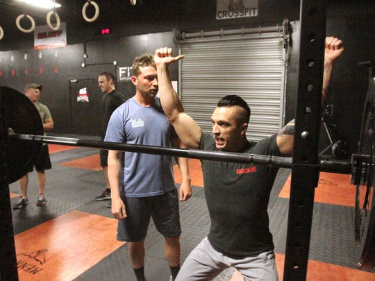 Owner and lead coach Gavin Dubetz, facing with arms up, demonstrates the proper safety technique to club member Zack Davis during a high-intensity workout at Crossfit Menace in Genoa Township.