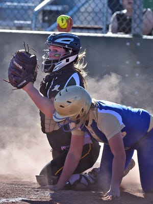 Bishop Manogue's Hailey Merlino throws to third for the double play after tagging Reed's Aliya Lange out at home during Thursday's game at Manogue.