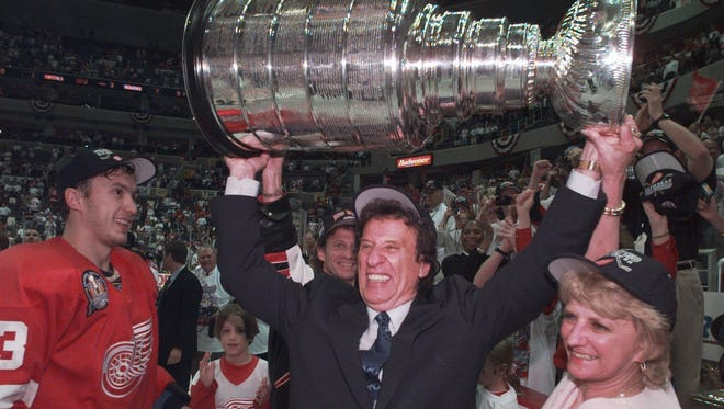 Red Wings owner Mike Ilitch, center, hoists the Stanley Cup after the team's second consecutive championship in 1998. No team has repeated in the NHL since.