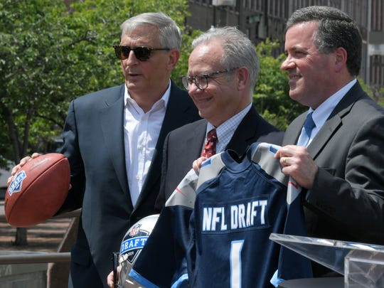 Nashville Convention & Visitors Corp. President and CEO Butch Spyridon, Mayor David Briley and Tennessee Titans Senior Vice President Stuart Spears pose for a photograph at 1st Ave and Broadway on Wednesday, May 23, 2018 after a press conference regarding the NFL's announced that Nashville will host the 2019 NFL Draft.