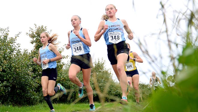 Jaden Theis, left, Lauren Cleary, middle, and Olivia Thies, right, have been key components in Lansing Catholic's success.