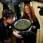 In this photograph taken Saturday with a fisheye lens, Rebecca Gasca, a consultant from Reno, Nevada, left, smells a bucket of marijuana opened by grow facility spokesperson Elan Nelson as a contingent of Nevada lawmakers, their staffers and a handful of lobbyists toured two retail and grow operations.