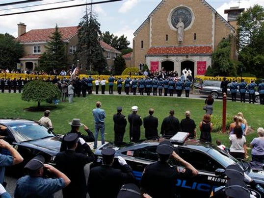 Police officers salute as the flag-draped casket of Waldwick police officer Christopher Goodell is carried into St. Luke's Church in Ho-Ho-Kus for a wake on Monday. (AP Photo/Mel Evans)