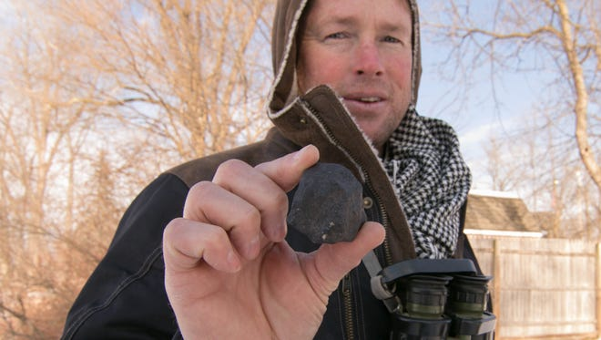 Robert Ward holds the largest of three meteorites he's found in a cluster on a lake in Hamburg Township Thursday, Jan. 18, 2018. He works with teams that travel the world in search of meteorites.
