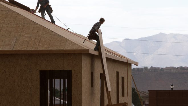 Construction workers add plywood to the roof of a home being built in the Washington Fields area in this file photo. An uptick in construction has helped drive job growth across Utah, according to the latest report from the Utah Department of Workforce Services.
