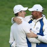 Europe's Thomas Bjorn congratulates Justin Rose on winning the hole and halving the match on the 18th green at the end of the foursomes match on the second day of the Ryder Cup golf tournament in Gleneagles, Scotland, on Saturday, Sept. 27, 2014.