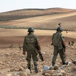 Turkish soldiers patrol as Islamic militants fight Kurdish forces to the west of Kobani, Syria, at the Turkey-Syria border on Tuesday, Sept. 30, 2014. U.S.-led coalition air strikes have targeted Islamic State fighters, vehicles and weapons on both sides of the Syria-Iraq frontier.