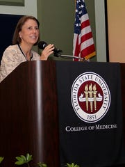 Dr. Katherine Grichnik presents two scholarships from