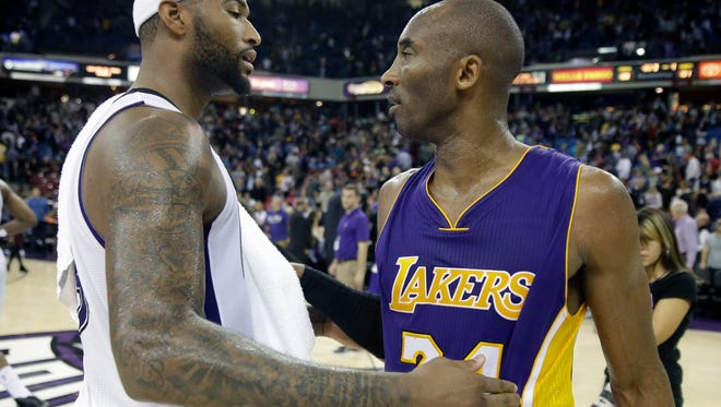 Sacramento Kings center DeMarcus Cousins, left, and Los Angeles Lakers Kobe Bryant talk after the Kings beat the Lakers 108-101 in an NBA basketball game in Sacramento, Calif., Sunday, Dec. 21, 2014.(AP Photo/Rich Pedroncelli)