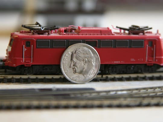 Tiny Z-gauge electric locomotive, hardly as high as the diameter of a dime, rides on miniature track.