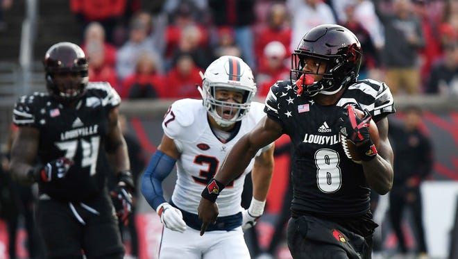 Louisville quarterback Lamar Jackson (8) runs 68 yards for the Cardinals first touchdown against Virginia on Saturday at Papa John's Cardinal Stadium.  Nov. 11, 2017