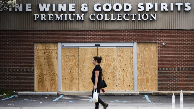 "A pedestrian walks past a boarded up Wine and Spirits store in Philadelphia, Friday, March 20, 2020. Pennsylvania Gov. Tom Wolf directed all ""non-life-sustaining"" businesses to close their physical locations late Thursday and said state government would begin to enforce the edict starting early Saturday. (AP Photo/Matt Rourke)"