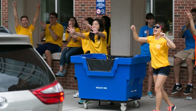 Student volunteers greet a new student at Susan B. Anthony Hall on move-in day for new students at the University of Rochester on August 25, 2015.