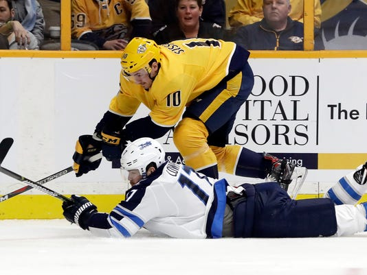 Winnipeg Jets center Adam Lowry (17) falls as he chases the puck with Nashville Predators center Colton Sissons (10) in the first period of an NHL hockey game, Monday, Nov. 20, 2017, in Nashville, Tenn. (AP Photo/Mark Humphrey)