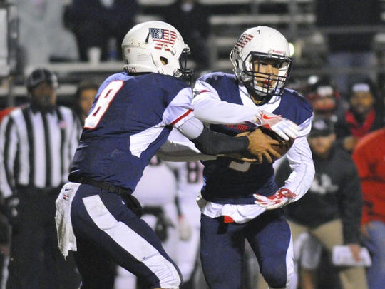 Tulare Western quarterback Andre Aguilar hands off to Keshon Butler in Friday's Central Section Division III semifinal playoff football game at Bob Mathias Stadium.