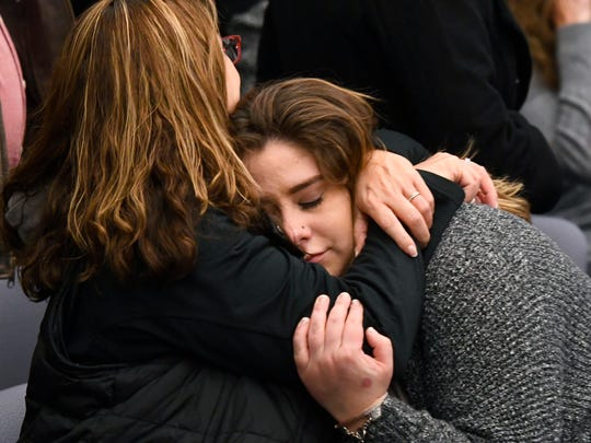 Former youth gymnast Alexis Alvarado, right, is hugged by family friend Deedee Hazen after former gymnastics doctor Larry Nassar pleaded guilty.