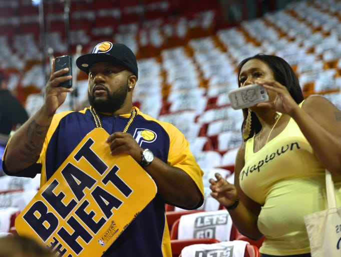 Brendan Powerll, of Indianapolis, and Synetra Payne, of Indianapolis, take photos court side before the start of the Indiana Pacers game against the Miami Heat during Game 6 of the Eastern Conference Finals inside AmericanAirlines Arena, Friday, May 30, 2014, in Miami, Fla.
