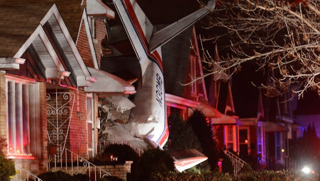 A small twin-engine cargo plane is seen after it crashed into a home on Chicago's southwest side early Tuesday, Nov. 18, 2014, shortly after taking off from Midway International Airport.