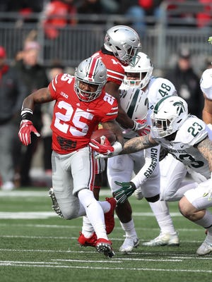 Ohio State's Mike Weber runs by Michigan State defenders in the second quarter Saturday, Nov. 11, 2017 at Ohio Stadium in Columbus, Ohio.