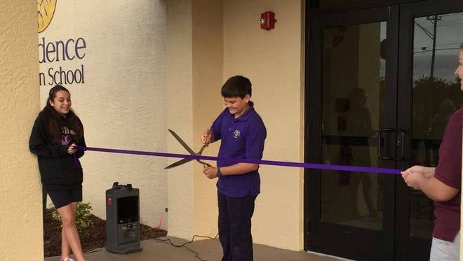 Zac Rullo, Student Government Association President at Providence Christian School, cuts the ribbon on a new addition at the school.
