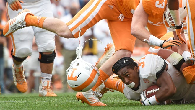 Tennessee running back Jayson Sparks (37) loses his helmet as he is tackled by long snapper Will Bradshaw (53) and other defenders during the Orange and White game Saturday at Neyland Stadium.