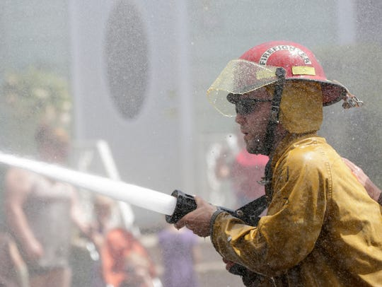 A Stratford firefighter sprays a barrel during a competition