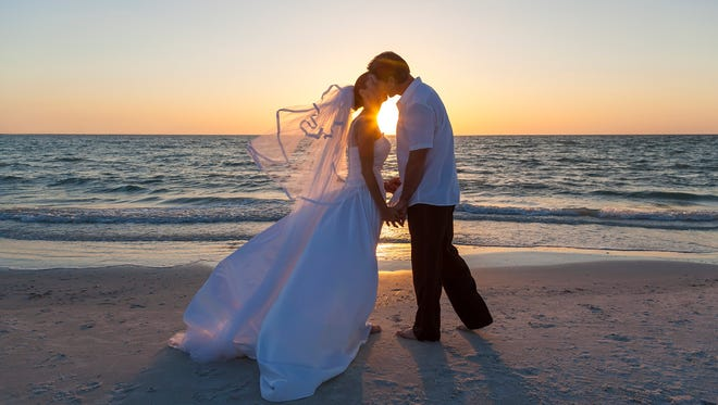 A married couple, bride and groom, kissing at sunset or sunrise on a beautiful tropical beach