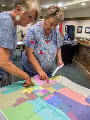 Poll workers Marie Thurston, left, and Bobbie Jensen, right, locate a voter's address on the precinct map of Iron County at the Cedar City Office Tuesday, June 26, 2018.