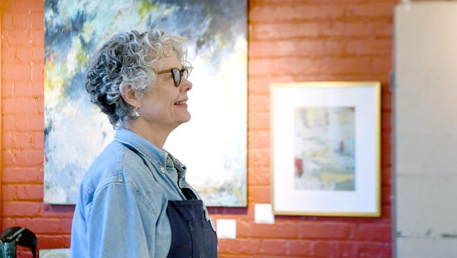 Cindy Walton takes a moment to step back and look at her works in progress hanging on the wall of her workspace in her studio in the River Arts District on Thursday, Feb. 8, 2018.